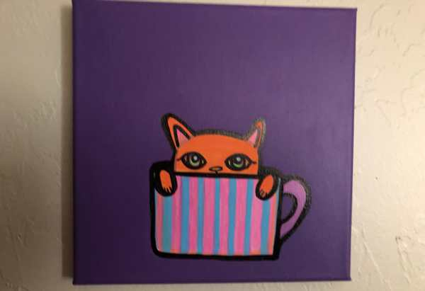 Orange cat in a pink and blue tea cup on a purple background.