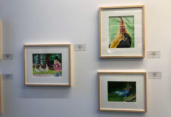 Framed paintings of a girl with geese, a rooster, and a Steller's jay